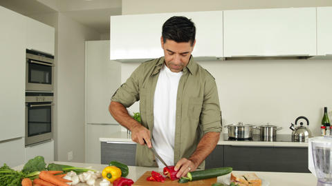 Handsome man chopping vegetables Footage