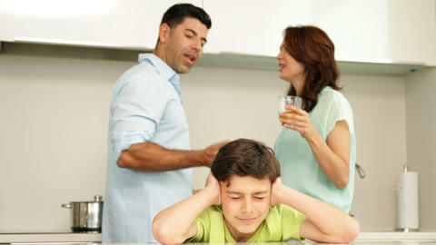 Upset boy covering his ears while his parents figh Footage
