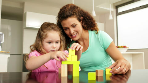Mother and daughter playing with building blocks a Footage