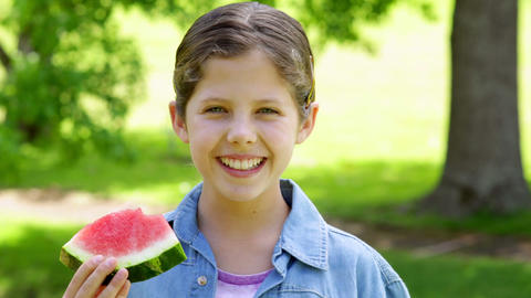 Cute little girl eating watermelon in the park Footage
