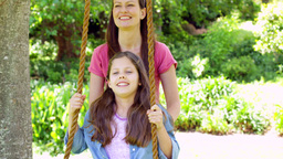Mother pushing her daughter on a swing in the play Footage
