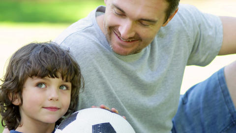 Father sitting with little son holding football in Footage