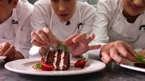 Line of chefs garnishing dessert plates with mint  Footage