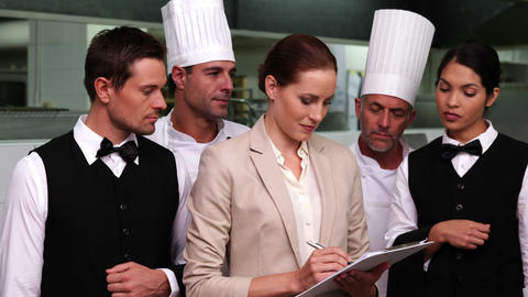 Serious Restaurant Staff With Manager Looking At C stock footage