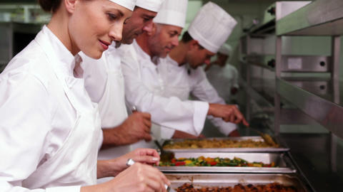 Row of chefs preparing food in serving trays Footage