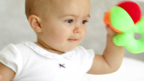 Cute baby girl playing with soft ball on bed Footage