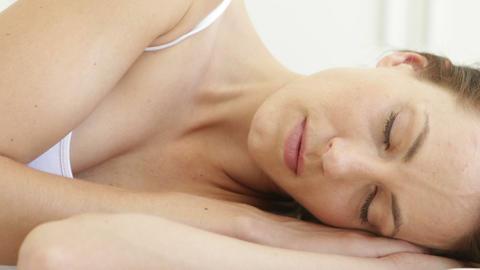 Beautiful brunette sleeping on her bed Footage
