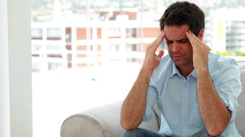 Casual man sitting on the sofa getting a headache Footage