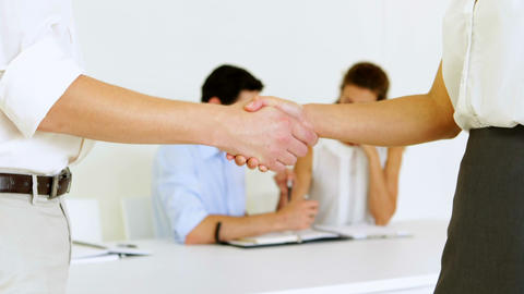 Business people shaking hands with colleagues behind them Footage