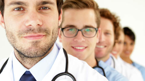 Team of doctors standing in row smiling at camera Footage