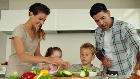 Parents preparing a salad with their children Footage