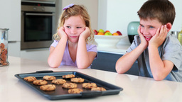Siblings waiting for hot cookies to cool down Footage
