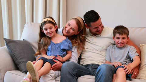 Happy young family sitting on sofa smiling at came Footage