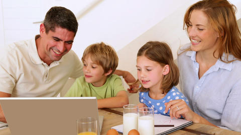 Happy family using laptop together at the breakfast table