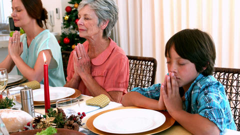 Extended family saying grace before christmas dinner Live Action
