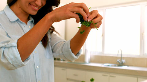 Woman adding chopped herbs to pot Footage