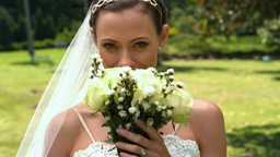 Bride smelling her bouquet in the park Footage