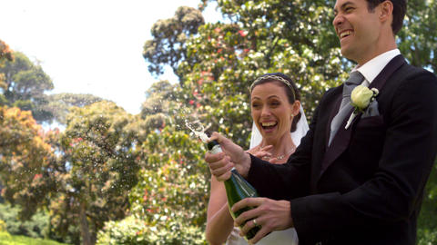 Groom popping bottle of champagne with new wife Footage