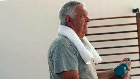 Elderly man lifting hand weights Footage