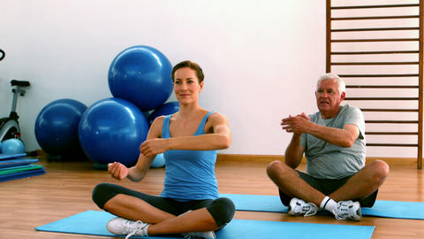 Elderly man sitting on mat exercising with instructor Footage