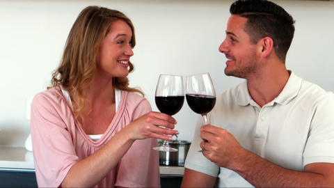 Happy couple having red wine in kitchen Footage