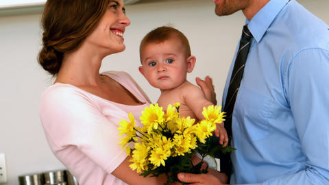 Mother holding baby with father holding yellow flowers Live Action