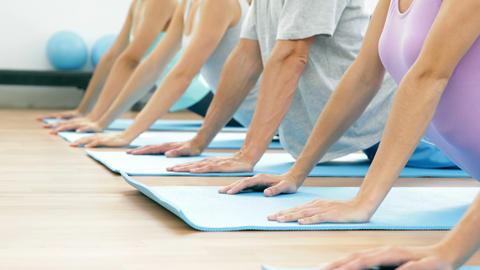 Yoga class lying on mats doing cobra pose Footage