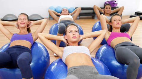 Fitness class sitting on exercise balls doing sit ups Live Action