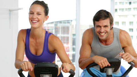 Fit couple exercising on bikes in fitness studio Footage