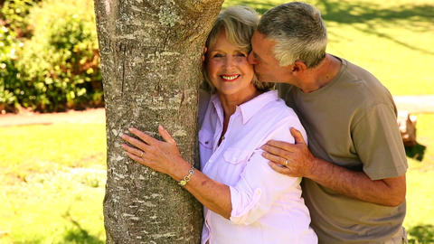 Retired Couple Leaning Against Tree Smiling At Cam stock footage