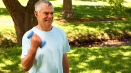 Retired Man Lifting Weights Outside stock footage