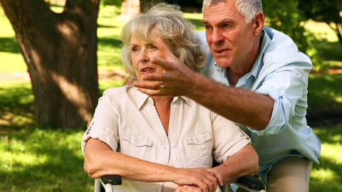 Retired Man Showing His Disabled Wife Something stock footage
