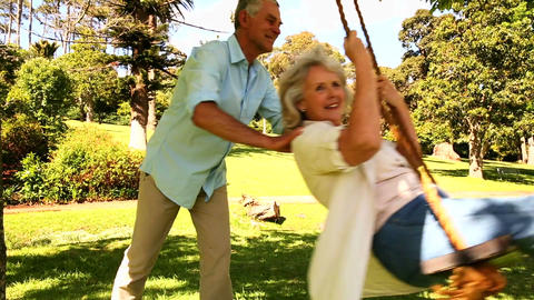 Retired man pushing his wife on swing Footage