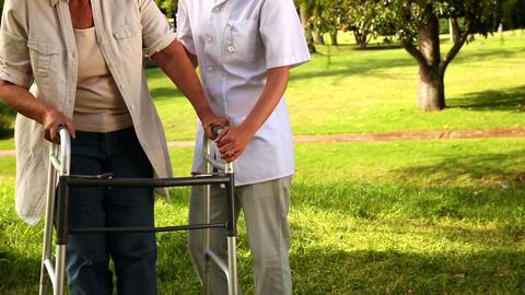 Nurse talking to woman using walker outside Footage