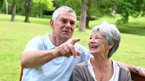 Retired couple sitting on a park bench talking and Footage