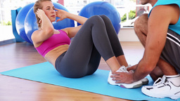 Fit woman doing sit ups with trainer Footage