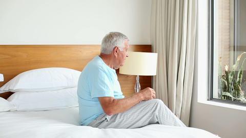 Senior man sitting on bed thinking Footage