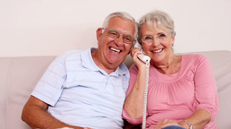 Senior couple sitting on sofa talking on the phone Footage