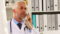 Doctor talking on the phone at his desk Footage
