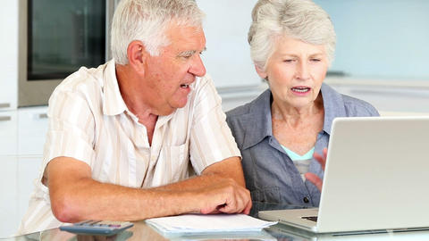 Senior couple using laptop to pay their bills Footage
