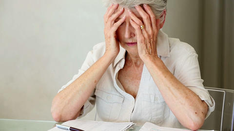 Senior woman sitting at table working out bills Footage