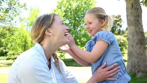Happy little girl telling her mother a secret in the park Footage
