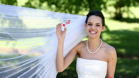 Beautiful bride blowing bubbles in the park Footage