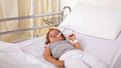 Little girl lying in hospital bed with a thermomet Footage