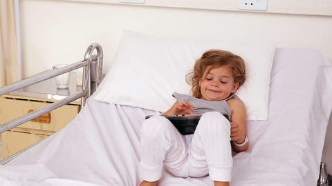 Little girl lying in hospital bed using a tablet Footage