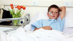 Little sick boy sitting in bed with thermometer Footage