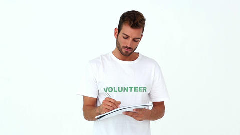 Handsome volunteer writing on notepad Live Action