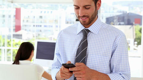 Man texting on phone while colleague works behind him Footage