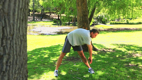 Man stopping his run to stretch in the park Footage