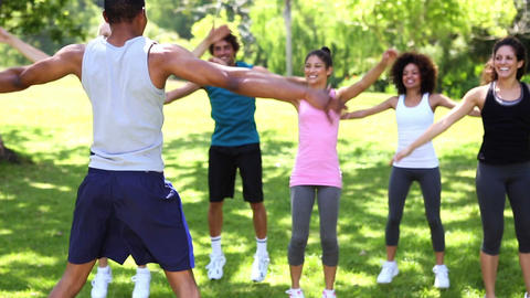 Fitness class doing jumping jacks in the park Footage